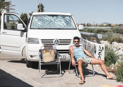 hombre descansa delante de furgoneta